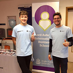 Two LAIBS students stood by a banner with their thumbs up