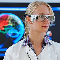 Scientist in lab coat and goggles, stood in front of a brain scan
