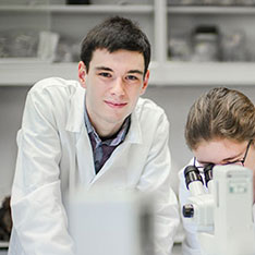Two students in lab coats, one looking into a microscope