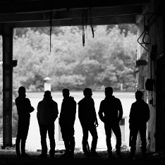A group of young men in silhouette beneath a bridge