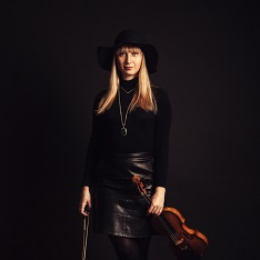 Alicja Smietana stood in front of a black background, holding a violin down by her hip.