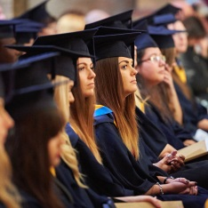 Students dressed in graduation robes sat together in an audience