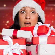 Woman in santa hat holding Christmas presents