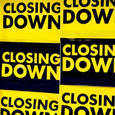 "A yellow and black sign that says ""Closing down""."