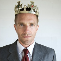 Man in a suit, wearing a crown