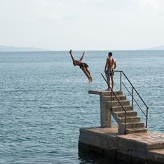 A person diving off a platform into the sea
