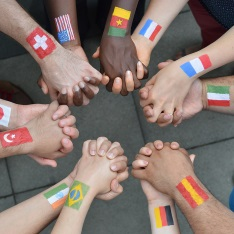 People holding hands with flags from different countries painted on their wrists