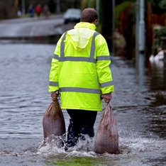Man carrying two sandbags on a flooded road