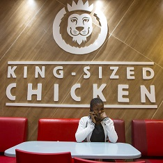 A Zambian teenager on the phone in a chicken shop