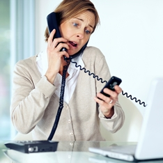A lady multi-tasking with a landline and mobile phone