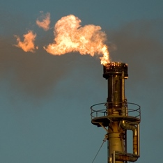 Oil production in progress with fire blasting out the top of a rig