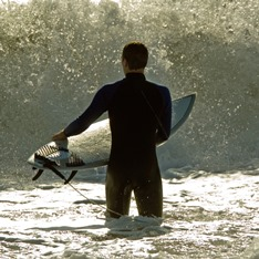 A man holding a surf board, standing in the sea