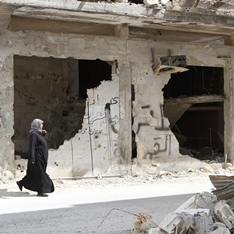 A woman walking through a ruined street in Homs, Syria