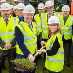 Staff members, including Vice Chancellor, Iain Martin, holding a shovel with turf on it.