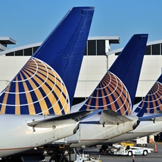 Three United Airlines aeroplane tail fins lined up at an airport