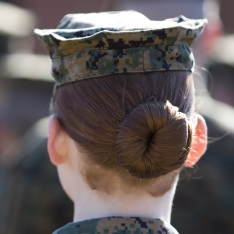 The back of a marine's head - wearing a cap and her hair in a bun.